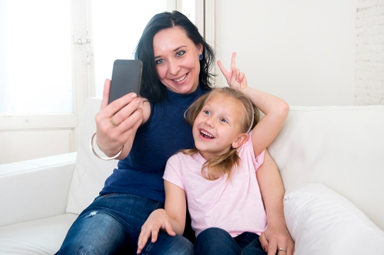 woman and little daughter taking selfie photo with mobile phone